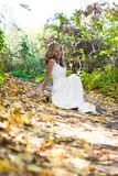 Happy bride in white dress on autumn sunny nature. Happy bride in white dress sitting on the footpath in autumn sunny nature Stock Images
