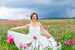 Happy bride in white dress  having fun in flower poppy field. Beautiful happy bride in white dress  having fun in flower poppy field on summer day. Just married Stock Image