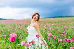 Happy bride in white dress having fun in flower poppy field stock photos