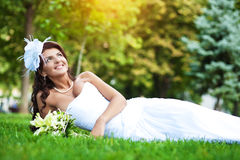 Happy bride in white dress lying on green grass Stock Images