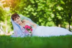 Happy bride in white dress lying on green grass Stock Photos