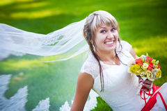 Happy bride in white dress near the green grass Royalty Free Stock Photos