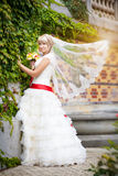 Happy bride in white dress near the green wall Royalty Free Stock Images