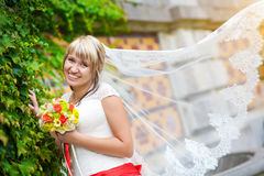 Happy bride in white dress near the green wall. Beautiful happy bride in white dress near the green wall Royalty Free Stock Photos