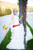 Happy bride in white dress near the palm tree. Beautiful happy bride in white dress near the palm tree Stock Images