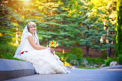 Happy bride in white dress is sitting on the curb Stock Images