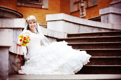 Happy bride in white dress sitting on the porch Royalty Free Stock Photo