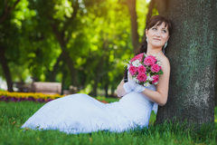 Happy bride in white dress sitting under a tree Stock Photos