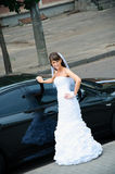 Happy bride in white dress standing near wedding car. Happy bride in a white dress standing near wedding car Royalty Free Stock Photo
