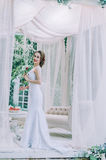 Happy bride in a white long dress, with a red rose in her hair,. Ouddors posing Royalty Free Stock Photos