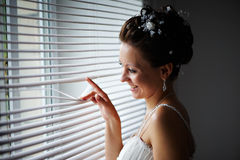 Happy bride at window Royalty Free Stock Images