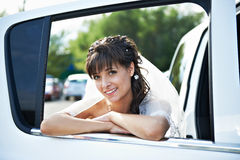 Happy bride in window of wedding limo Royalty Free Stock Photography