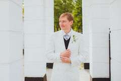 The happy bridegroom in a white jacket. Happy romantic young groom on the wedding day. Ceremonial men's wedding fashion royalty free stock image