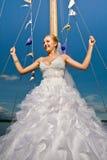 Happy brideposing at yacht mast agaisnt blue sky Stock Photos