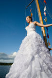 Happy brideposing at yacht mast agaisnt blue sky Royalty Free Stock Images