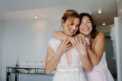 Happy bridesmaid giving a tender hug to bride. In hotel room. Asian women embracing her friend on her wedding day stock images