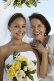 Happy Bridesmaid And Mother With Flower Bouquet. Portrait of happy bridesmaid and mother with flower bouquet outdoors Stock Image