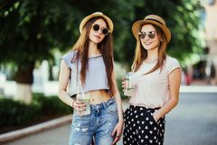 Happy positive moments of two stylish girls hugging with cocktails on street in city. Closeup portrait funny joyful attarctive you stock photos