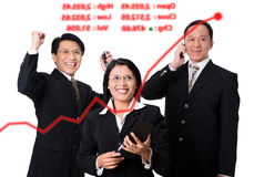 Happy brokers. Three executives who express their happiness when the stock price arise that appear on clear display. At the full resolution you can change the Royalty Free Stock Photography