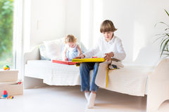 Happy brother and baby sister opening their presents. On a sunny room royalty free stock photo