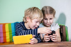 Happy brother helping sister to play with cellphone, indoor Royalty Free Stock Photography