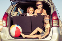 Happy brother and his two sisters are sitting in the car Stock Image