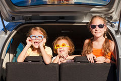 Happy brother and his two sisters are sitting in the car Royalty Free Stock Photos