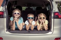 Happy brother and his two sisters are sitting in the car at the. Day time. Children having fun outdoors. Concept of the family is ready for travel royalty free stock photography