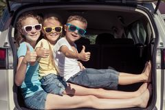 Happy brother and his two sisters are sitting in the car at the Stock Photography