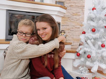 Happy brother hugging his sister near a christmas tree Royalty Free Stock Photos