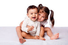 Happy brother and sister. Cute lovely toddler sister hugging happy baby brother while sitting, family friendship concept, on white Stock Image