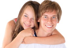 Happy brother and sister. Happy young man with youngster sister putting arms around shoulder, white background royalty free stock photo
