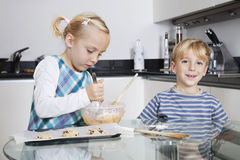 Happy brother and sister baking cookies in kitchen Royalty Free Stock Image