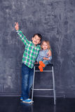 Happy brother and sister. Boy hugging sister on the background of a concrete wall Royalty Free Stock Photos