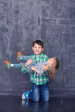 Happy brother and sister. Boy hugging sister on the background of a concrete wall Stock Photos