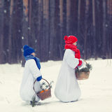 Happy brother and sister in costumes snowman walking in winter forest, Royalty Free Stock Image