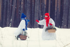 Happy brother and sister in costumes snowman walking in winter forest, Royalty Free Stock Images
