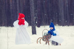 Happy brother and sister in costumes snowman walking in winter forest, Stock Images