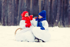 Happy brother and sister in costumes snowman walking in winter forest Royalty Free Stock Images