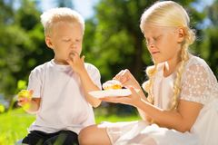Happy brother and sister eating a cake in the park stock photo