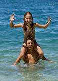 Happy brother and sister in fun on sea. Brother and sister (on shoulder - piggy back) in summer vacation in Adriatic sea (Omis Croatia). Vertical color photo Royalty Free Stock Photography