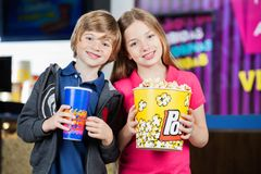 Happy Brother And Sister Holding Snacks At Cinema Stock Photography