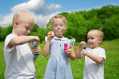 Happy brother and sister inflate soap bubbles Stock Photos