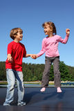 Happy brother and sister jump on trampoline. On sunny summer day royalty free stock photo