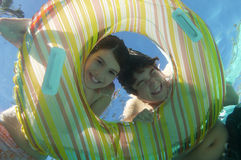 Happy Brother And Sister Looking Through Inflatable Ring Stock Image
