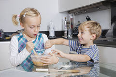 Happy brother and sister mixing batter together in kitchen Royalty Free Stock Photo
