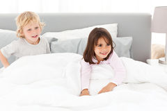 Happy brother and sister playing in a bed Royalty Free Stock Photo