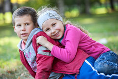 Happy brother and sister playing together in summer park Royalty Free Stock Image