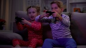 Happy brother and sister playing video game at night sitting sofa, addiction. Stock photo stock photo