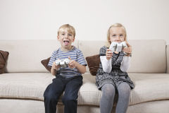 Happy brother and sister playing video game on sofa Royalty Free Stock Image